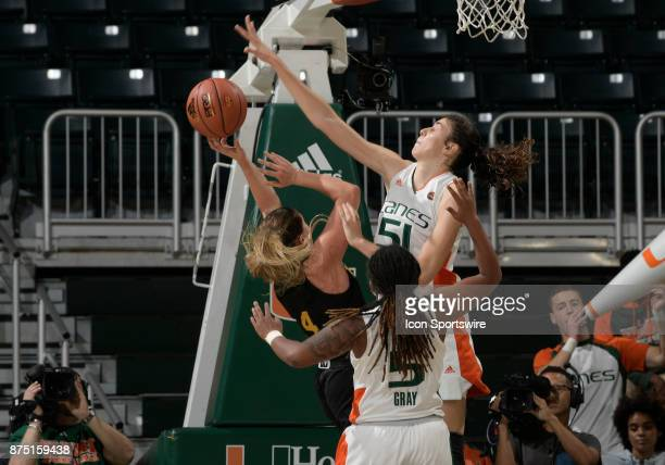 Miami center SerenaLynn Geldof defends the shot of guard Hayley Robertson during a women's college basketball game between the University of Vermont...
