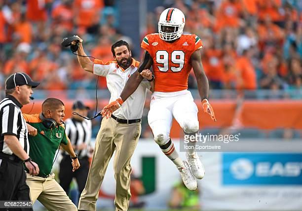 Miami defensive lineman Joe Jackson and Miami Defensive Coordinator Manny Diaz celebrate during an NCAA football game between the Duke University...