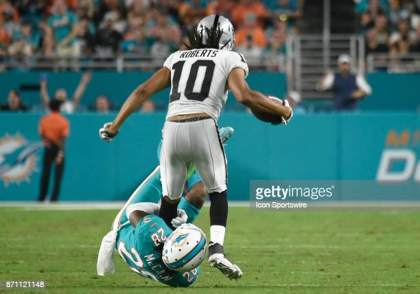 Miami Dolphins corner back Bobby McCain tackles Oakland Raiders wide receiver Seth Roberts during an NFL football game between the Oakland Raiders...
