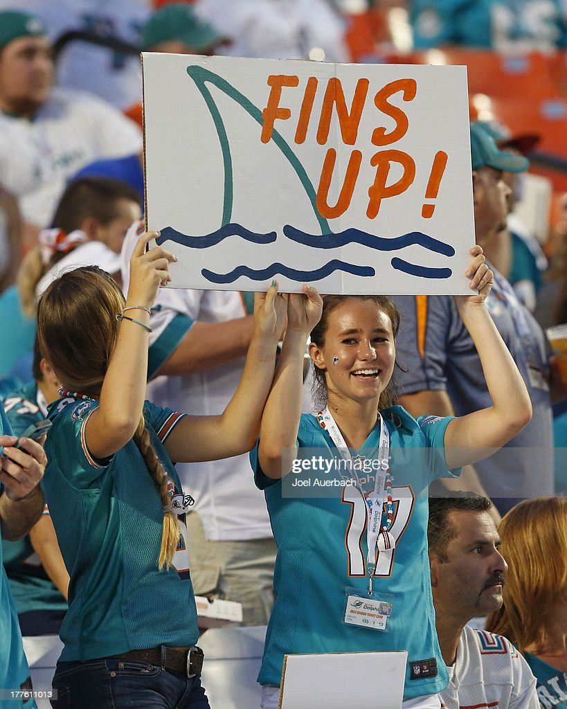 Miami Dolphins fans hold up a sign supporting the team prior to the game against the Tampa Bay Buccaneers during a preseason game on August 24, 2013 at Sun Life Stadium in Miami Gardens, Florida. The Buccaneers defeated the Dolphins 17-16.