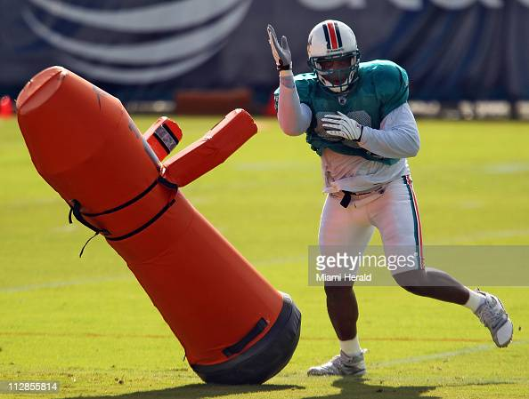 Miami Dolphins linebacker Quentin Moses takes down a tackling dummy in drills during Dolphins training camp at Nova Southeastern University Friday...