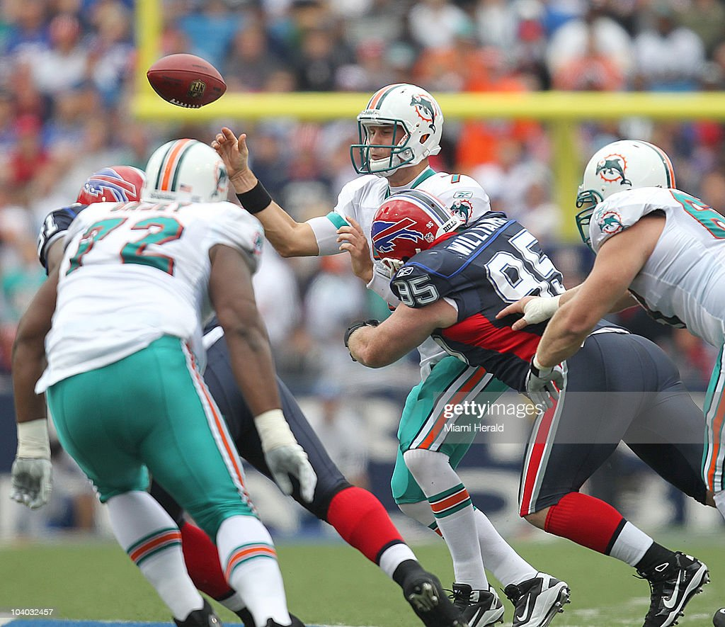 Miami Dolphins quarterback Chad Henne throws a pass while in the grasp of nose tackle <a gi-track='captionPersonalityLinkClicked' href=/galleries/search?phrase=Kyle+Williams+-+American+Football+Defensive+Tackle&family=editorial&specificpeople=9642838 ng-click='$event.stopPropagation()'>Kyle Williams</a> in the first quarter at Ralph Wilson Stadium in Buffalo, New York on Sunday, September 12, 2010.