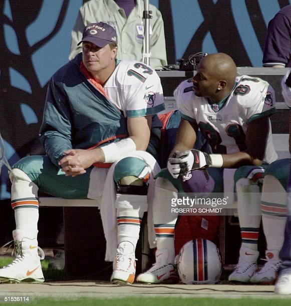 Miami Dolphins' quarterback Dan Marino and receiver OJ McDuffie sit on the bench during the final moments of their AFC Divisional playoff against the...