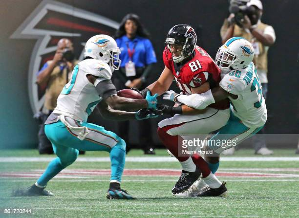 Miami Dolphins' Reshad Jones intercepts the ball from Atlanta Falcons' Austin Hooper with help from Cordrea Tankersley late in the fourth quarter on...