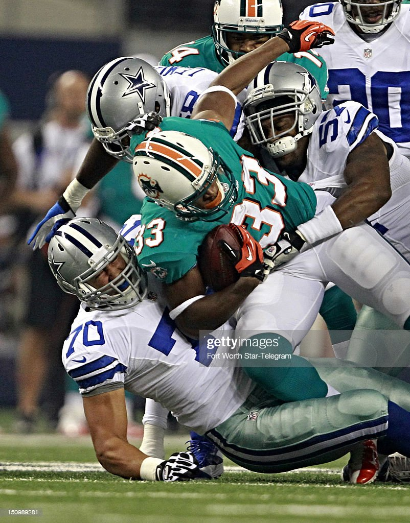 Miami Dolphins running back Daniel Thomas (33) is stopped by the Dallas Cowboys defense, including Victor Butler (57) and Tyrone Crawford (70), in the first quarter of NFL preseason action on Wednesday, August 29, 2012, at Cowboys Stadium in Arlington, Texas.