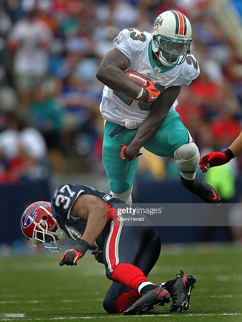 Miami Dolphins running back Ronnie Brown leaps over a Buffalo Bills free safety George Wilson in the second quarter at Ralph Wilson Stadium in Buffalo, New York on Sunday, September 12, 2010.