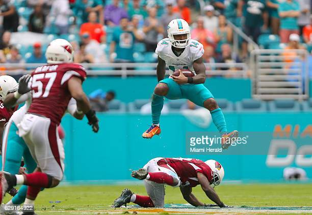 Miami Dolphins wide receiver Jarvis Landry leaps over Arizona Cardinals running back Kerwynn Williams in the second quarter of an NFL football game...