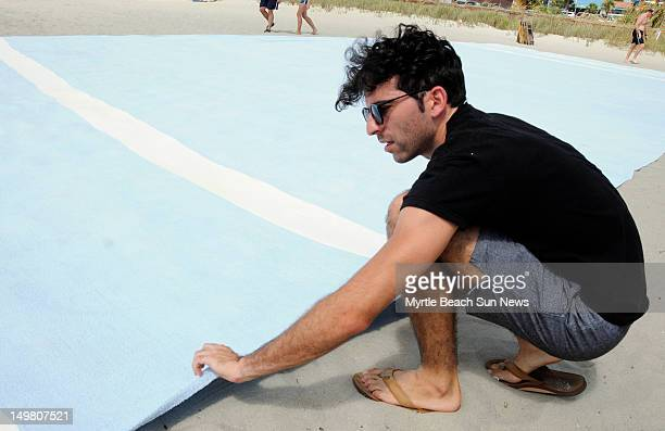 Miami Floridabased performance artist Misael Soto unfolds his giant beach towel he constructed measuring 56x29 feet on the beach just north of Plyler...