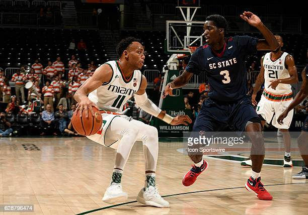 Miami guard Bruce Brown is guarded by South Carolina State guard Greg Mortimer i during an NCAA basketball game between the South Carolina State...