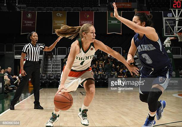 Miami guard Laura Cornelius is guarded by Maine guard Naira Caceres during an NCAA basketball game between the University of Maine Black Bears and...