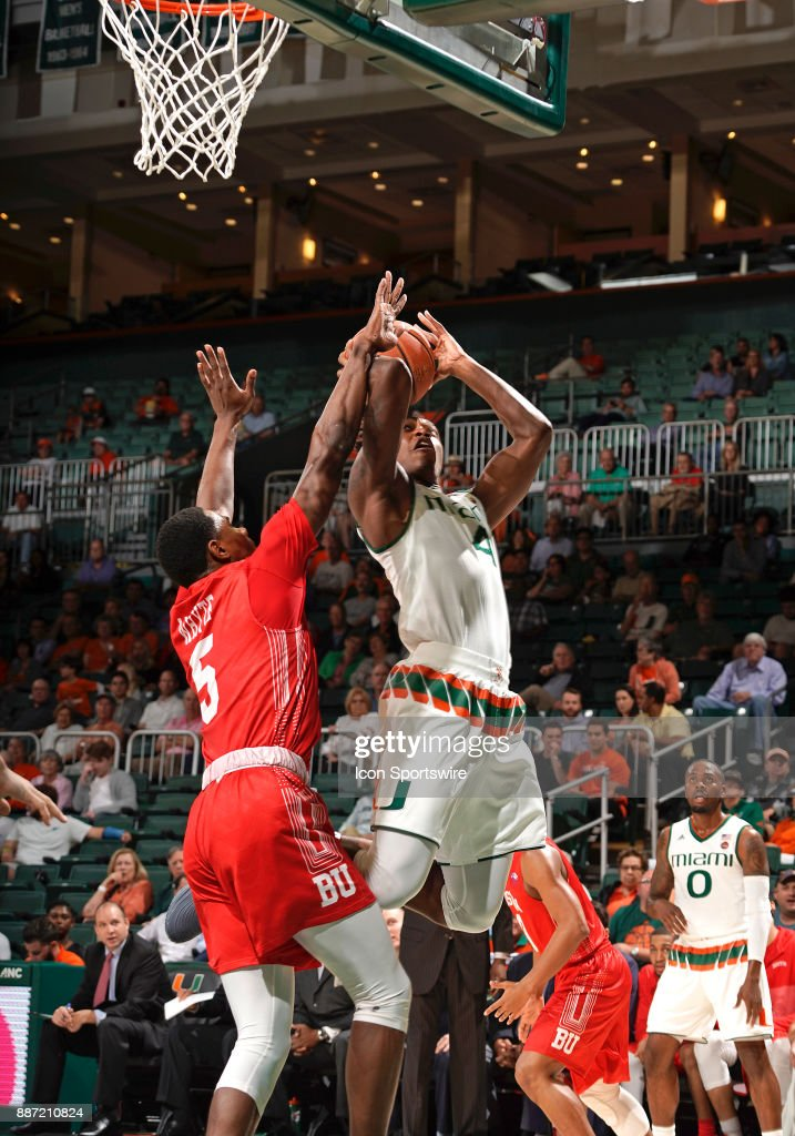 Miami guard Lonnie Walker IV (4) shoots against Boston U guard/forward Walter Whyte (5) during a college basketball game between the Boston University Terriers and the University of Miami Hurricanes on December 5, 2017 at the Watsco Center, Coral Gables, Florida. Miami defeated Boston U