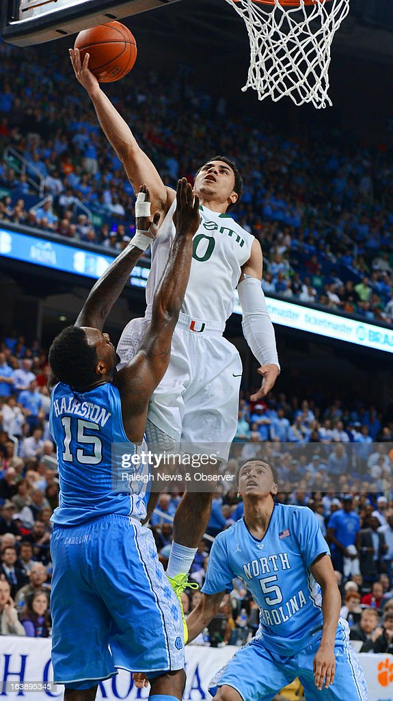 Miami guard Shane Larkin (0) goes in to score two of his game high 28 points as UNC guard P.J. Hairston (15) defends in the second half. The Miami Hurricanes defeated the North Carolina Tar Heels, 87-77, in the finals of the men's ACC basketball tournament at the Greensboro Coliseum in Greensboro, North Carolina, Sunday, March 17, 2013.