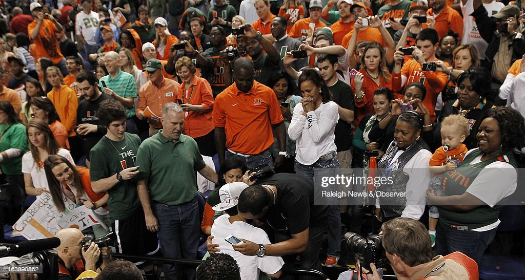 Miami guard Shane Larkin (0) hugs his dad at the end of the game. The Miami Hurricanes defeated the North Carolina Tar Heels, 87-77, in the finals of the men's ACC basketball tournament at the Greensboro Coliseum in Greensboro, North Carolina, Sunday, March 17, 2013.