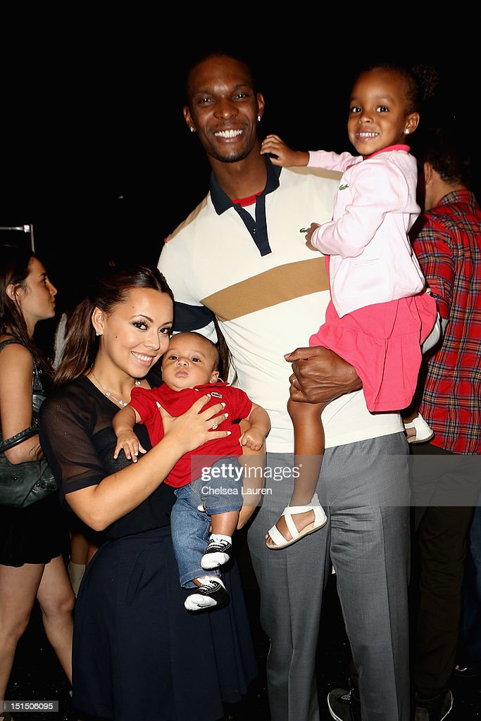 Miami Heat basketball player <a gi-track='captionPersonalityLinkClicked' href=/galleries/search?phrase=Chris+Bosh&family=editorial&specificpeople=201574 ng-click='$event.stopPropagation()'>Chris Bosh</a> (C) and wife Adrienne Bosh pose backstage at the Lacoste Spring 2013 fashion show during Mercedes-Benz Fashion Week at The Theatre, Lincoln Center on September 8, 2012 in New York City.