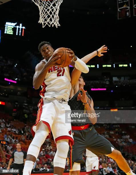 Miami Heat center Hassan Whiteside pulls down a rebound against Atlanta Hawks forward Ersan Ilyasova during the first quarter of an NBA preseason...