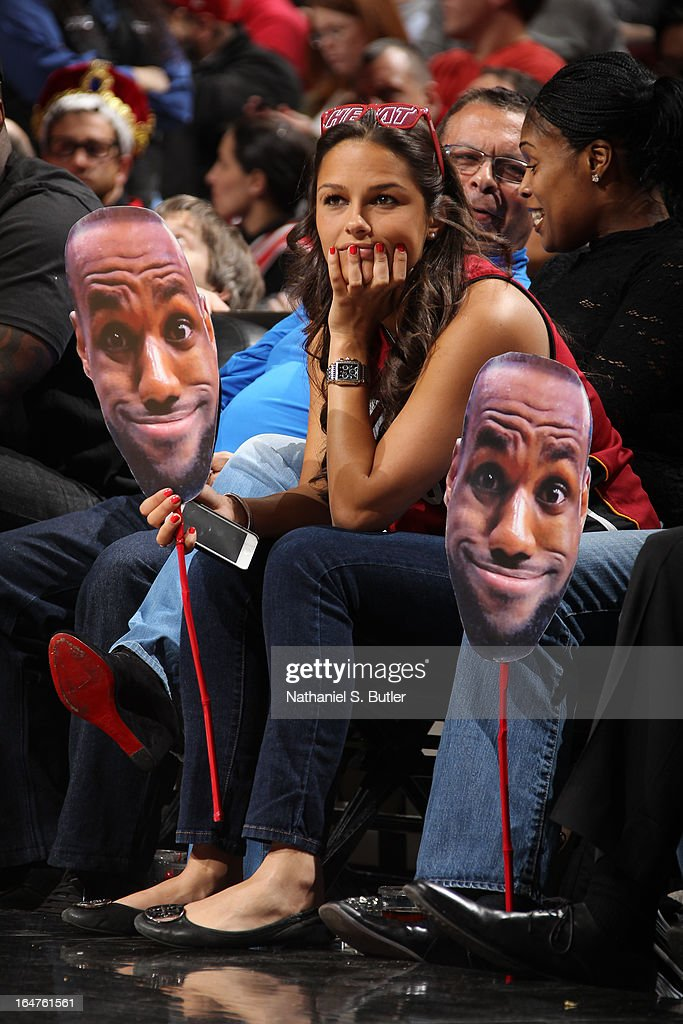 A Miami Heat fan sits courtside with cutouts of LeBron James #6 of the Heat during the game against the Chicago Bulls on March 27, 2013 at the United Center in Chicago, Illinois.