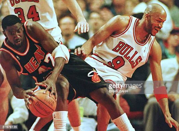 Miami Heat forward Walt Williams and Chicago Bulls guard Ron Harper fall in opposite directions after colliding in the first quarter 04 April at the...