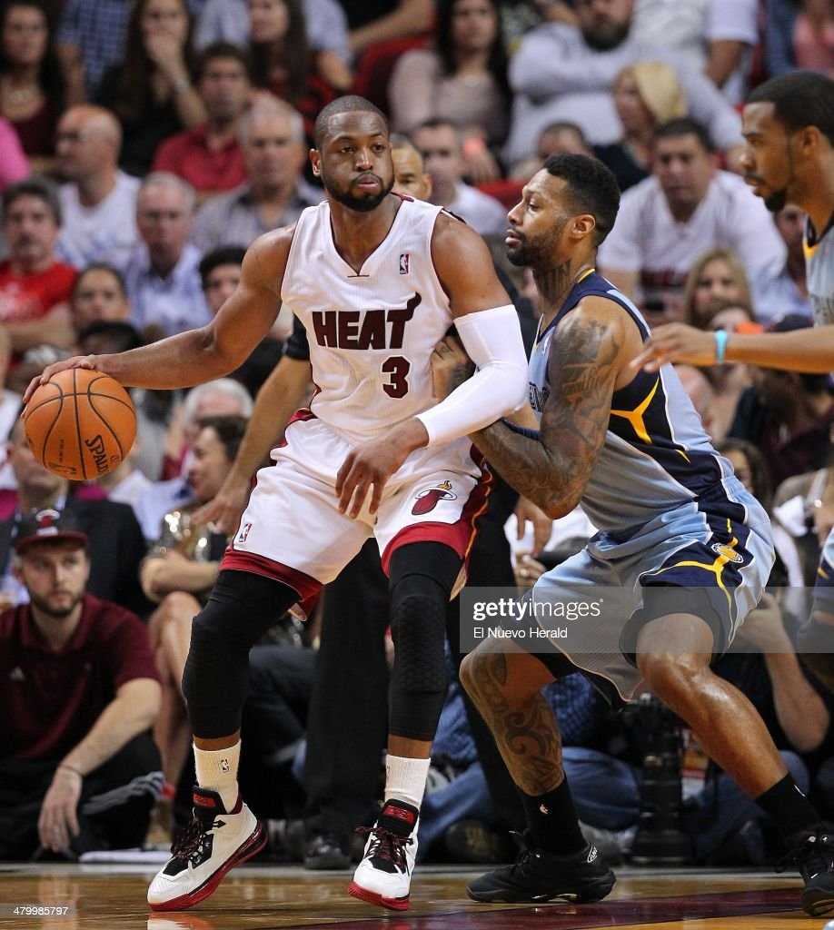Miami Heat guard Dwyane Wade dribbles against Memphis Grizzlies forward James Johnson during the second quarter at the AmericanAirlines Arena in...
