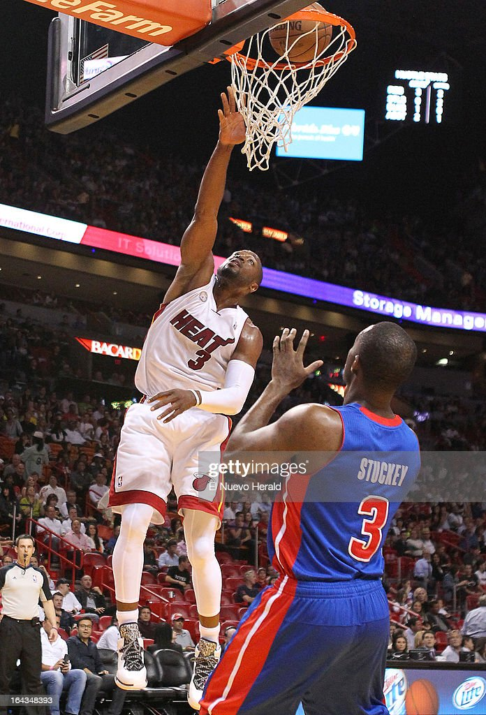 Miami Heat guard Dwyane Wade dunks against the Detroit Pistons' Rodney Stuckey in the first quarter at the American Airlines Arena in Miami, Florida, Friday, March 22, 2013.