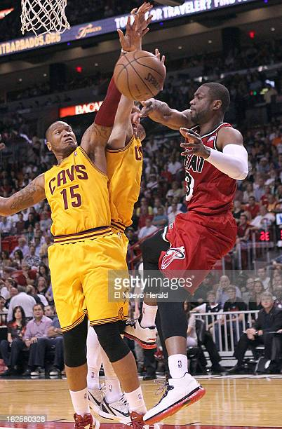 Miami Heat guard Dwyane Wade passes the ball against Cleveland Cavaliers defenders Marreese Speights left and Luke Walton in the second quarter at...