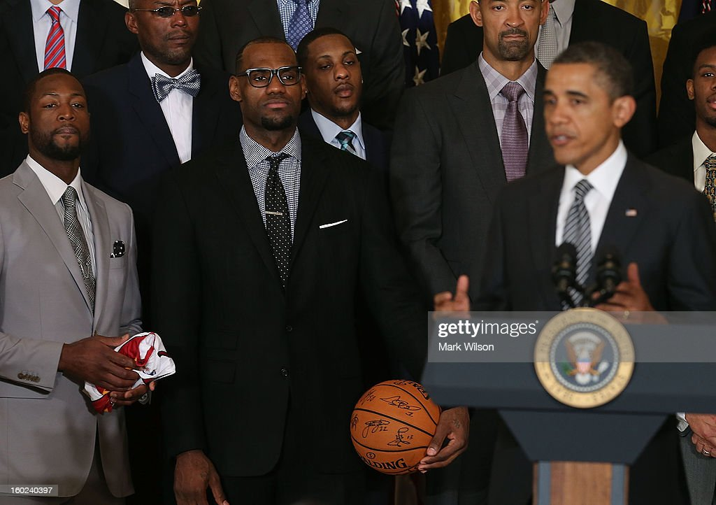 Miami Heat player Dwyane Wade (L) and LeBron James (C) listen to U.S. President Barack Obama (R) speak during an event to honor the NBA champion Miami Heat in the East Room at the White House on January 28, 2013 in Washington, DC. President Barack Obama congratulated the 2012 NBA champions for claiming their third NBA Championship by beating the Boston Celtics.