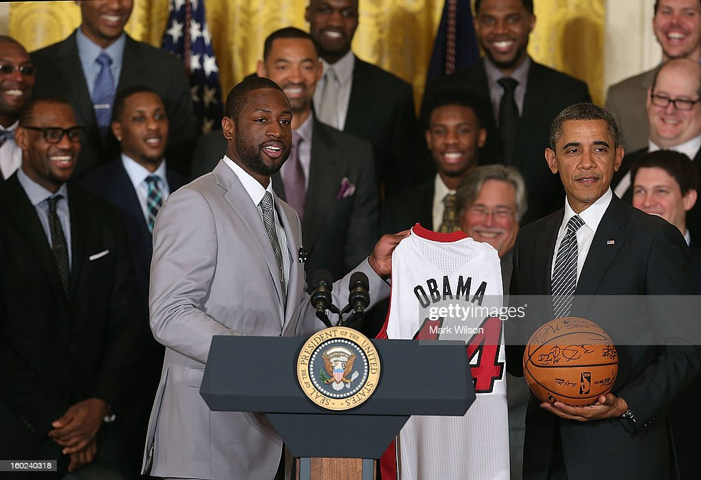 Miami Heat player Dwyane Wade presents U.S. President Barack Obama (R) with a jersey during an event to honor the NBA champion Miami Heat in the East Room at the White House on January 28, 2013 in Washington, DC. President Barack Obama congratulated the 2012 NBA champions for claiming their third NBA Championship by beating the Boston Celtics.