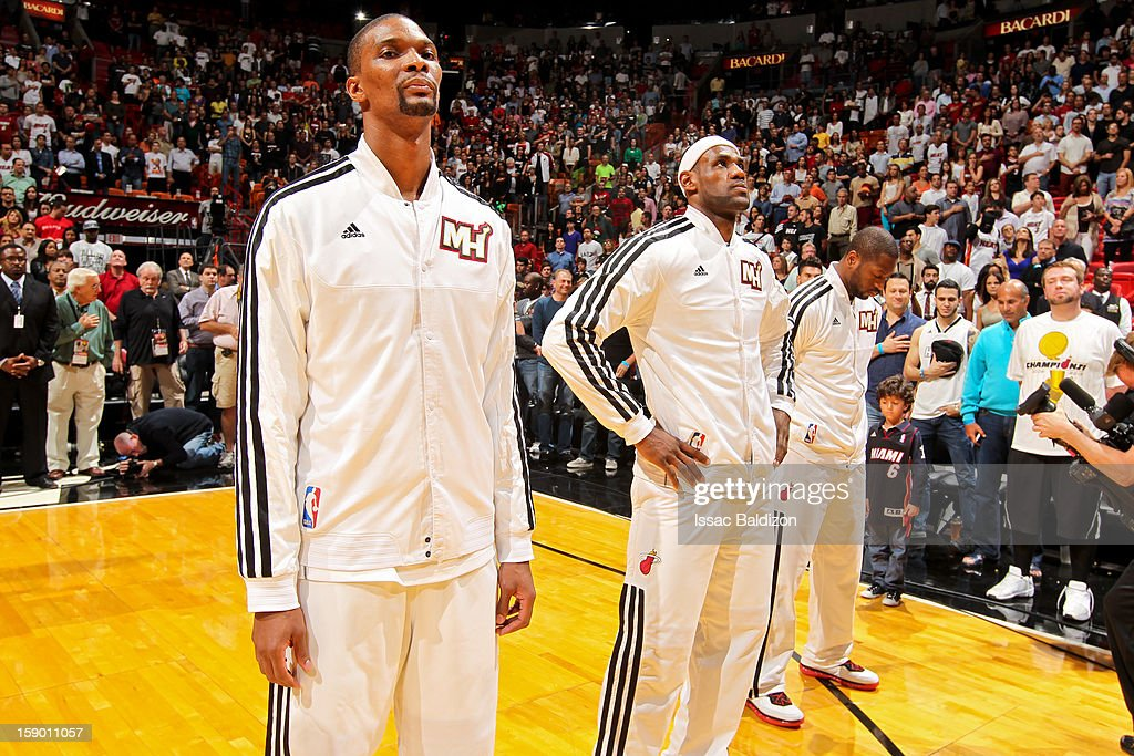 Miami Heat players, from left, Chris Bosh #1, LeBron James #6 and Dwyane Wade #3 listen to the National Anthem before playing against the Chicago Bulls on January 4, 2013 at American Airlines Arena in Miami, Florida.