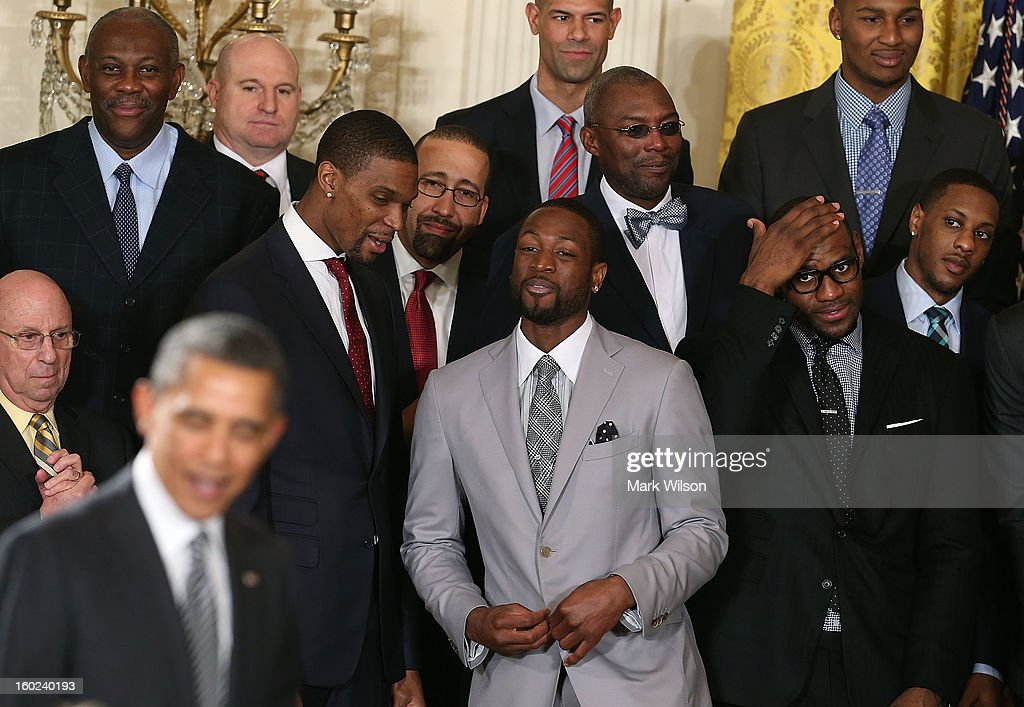Miami Heat players, including Dwyane Wade (C), LeBron James (R), and Chris Bosh (2L) watch as U.S. President Barack Obama (L) greets guests during an event to honor the NBA champion Miami Heat in the East Room at the White House on January 28, 2013 in Washington, DC. President Barack Obama congratulated the 2012 NBA champions for claiming their third NBA Championship by beating the Boston Celtics.