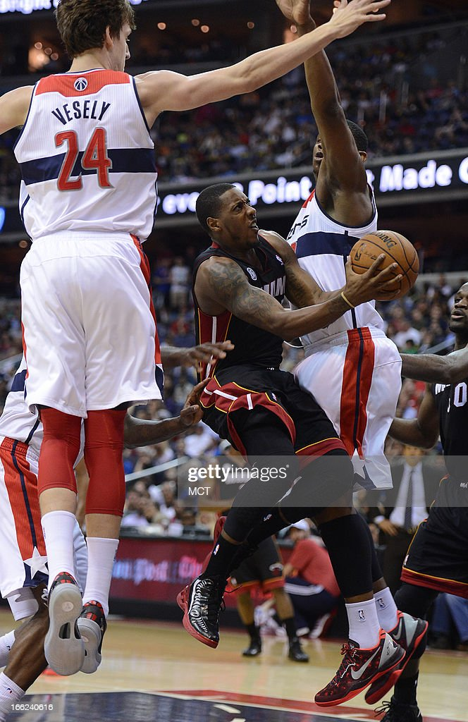 Miami Heat point guard Mario Chalmers (15) drives to the basket between Washington Wizards small forward Jan Vesely (24) and Washington Wizards power forward Kevin Seraphin (13) in the second quarter at the Verizon Center in Washington, D.C., Wednesday, April 10, 2013.