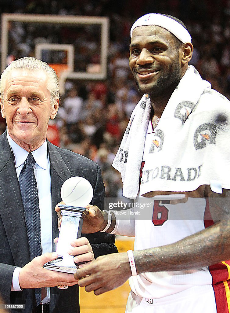 Miami Heat president Pat Riley gives the trophy of USA Basketball Male Athlete of Year to the team's LeBron James in a ceremony during halftime against the Dallas Mavericks at the AmericanAirlines Arena in Miami, Florida, on Wednesday, January 2, 2013.