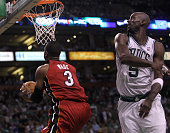 Miami Heat shooting guard Dwyane Wade slips up and under the defense of Boston Celtics power forward Kevin Garnett of a layup during the fourth...