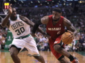 Miami Heat small forward LeBron James blows past Boston Celtics power forward Brandon Bass as he drives to the hoop en route to a spectacular 45point...