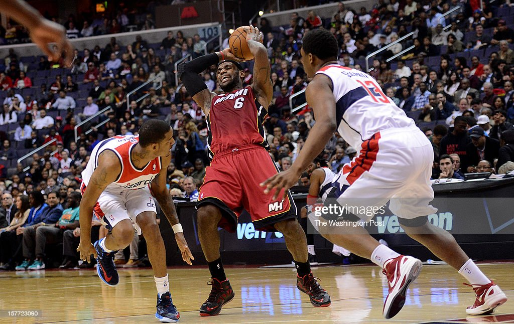 Miami Heat small forward LeBron James (6) is off balance as Washington Wizards small forward Trevor Ariza (1), left, and Washington Wizards power forward Kevin Seraphin (13), right, defend during the game at the Verizon Center on Tuesday, December 4, 2012.