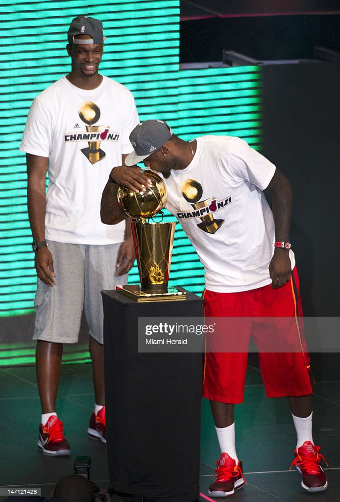Miami Heat's Chris Bosh, left, looks on as teammate LeBron James kisses the NBA Championship trophy as the Miami Heat celebrate their NBA world championship with their fans at the American Airlines Arena in Miami, Florida, Monday, June 25, 2012.