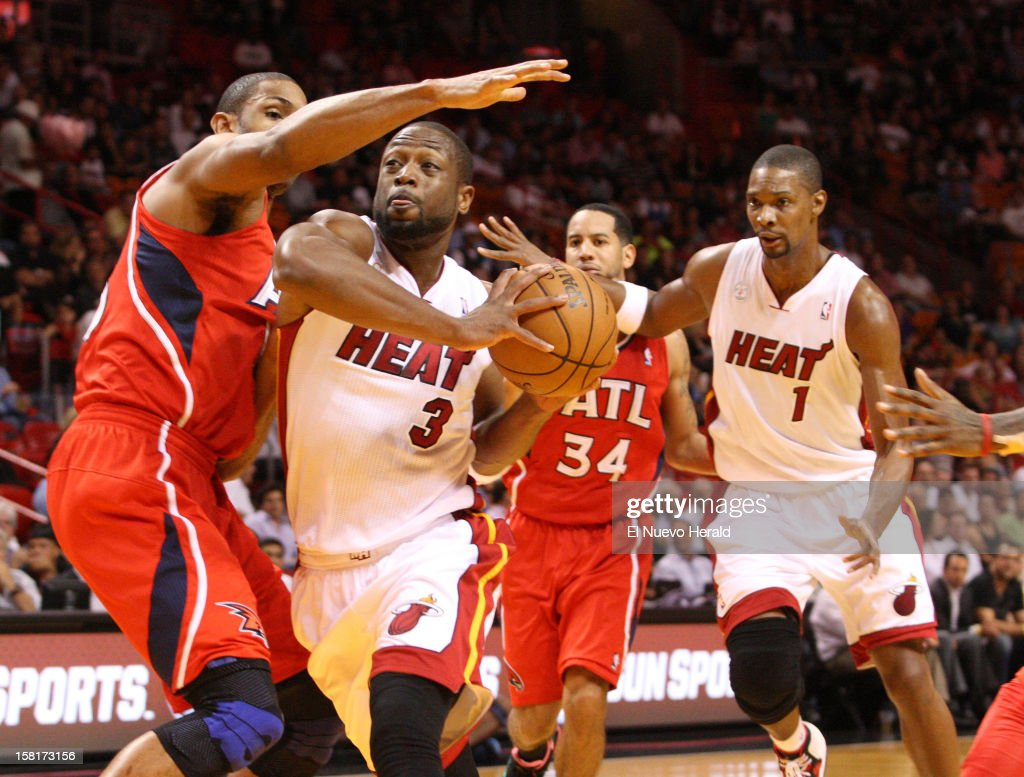 Miami Heat's Dwyane Wade goes to the basket against Atlanta Hawks' Al Horford during the first half at American Airlines Arena on Monday, December 10, 2012, in Miami, Florida.
