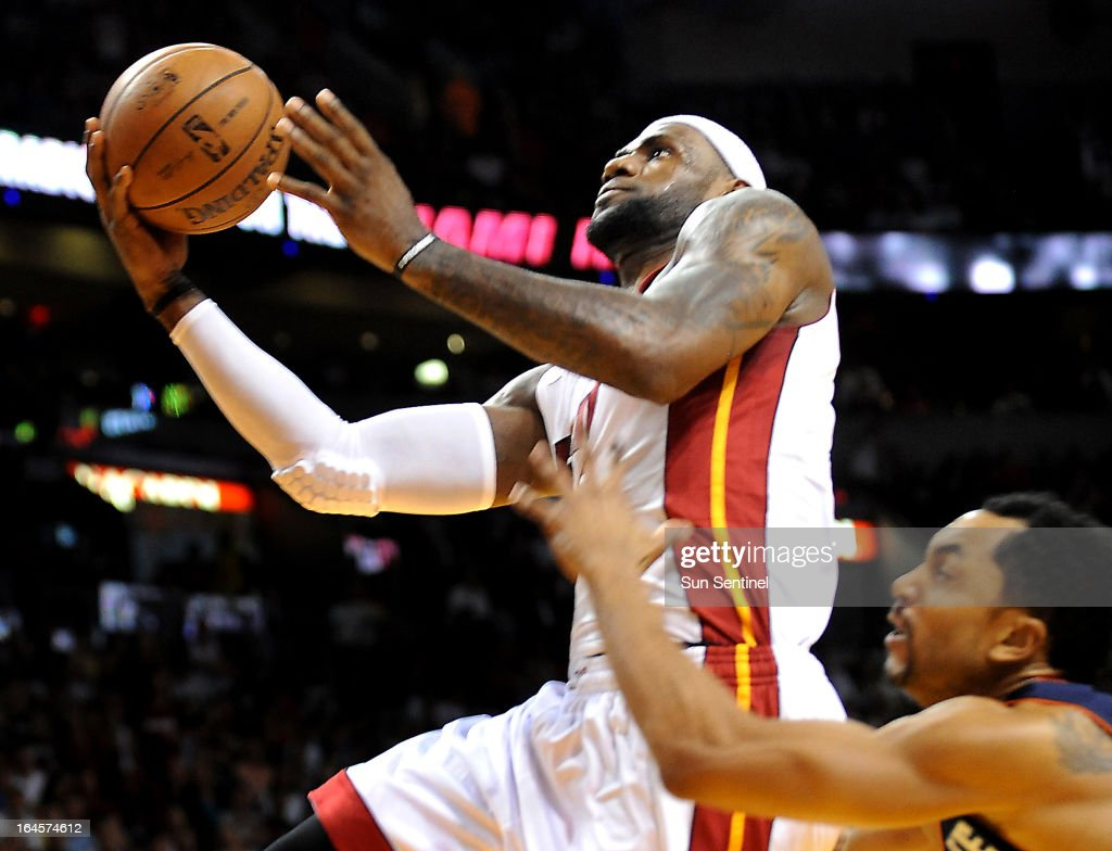 Miami Heat's LeBron James drives to the basket past Charlotte Bobcats' Gerald Henderson at AmericanAirlines Arena in Miami, Florida, Sunday, March 24, 2013.