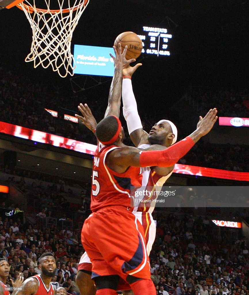 Miami Heat's LeBron James shoots over Atlanta Hawks' Josh Smith during the first half at American Airlines Arena on Monday, December 10, 2012, in Miami, Florida.