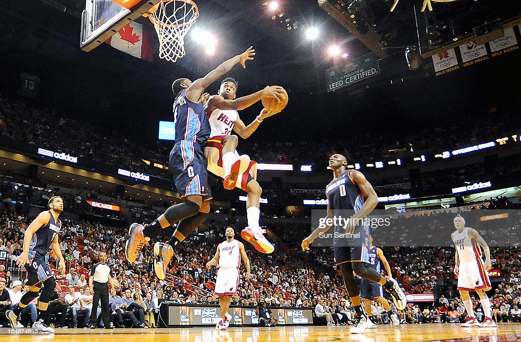 Miami Heat's Norris Cole takes flight as Charlotte Bobcats' Michael Kidd-Gilchrist defends at AmericanAirlines Arena in Miami, Florida, Sunday, March 24, 2013.