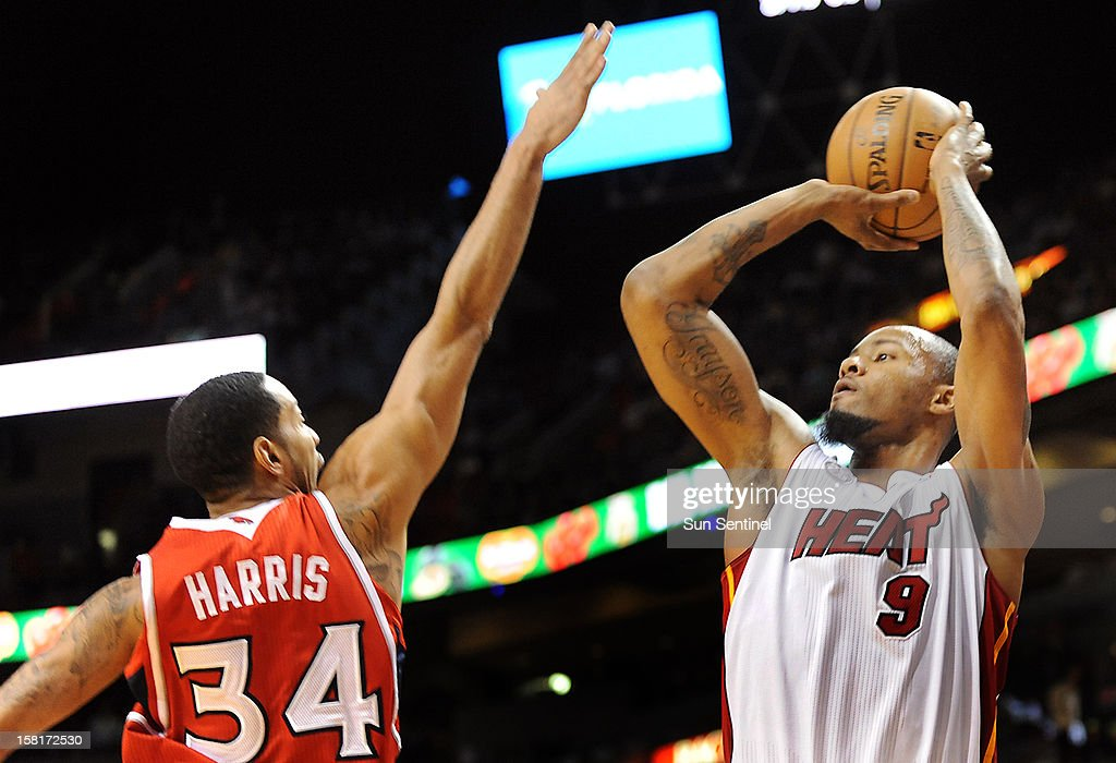 Miami Heat's Rashard Lewis takes a jump shot over Atlanta Hawks' Devin Harris at American Airlines Arena on Monday, December 10, 2012, in Miami, Florida.