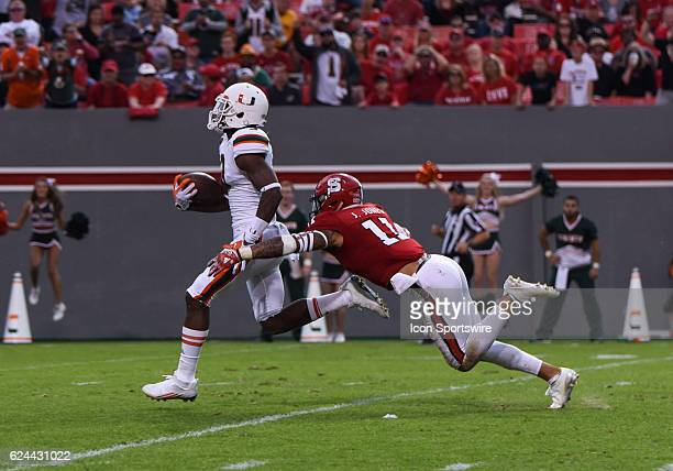 Miami Hurricanes wide receiver Stacy Coley runs after a long catch before being tackled by North Carolina State Wolfpack safety Josh Jones during the...