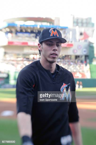 Miami Marlins center fielder Christian Yelich signs tosses a ball to a fan prior to an MLB game between the Miami Marlins and the Washington...