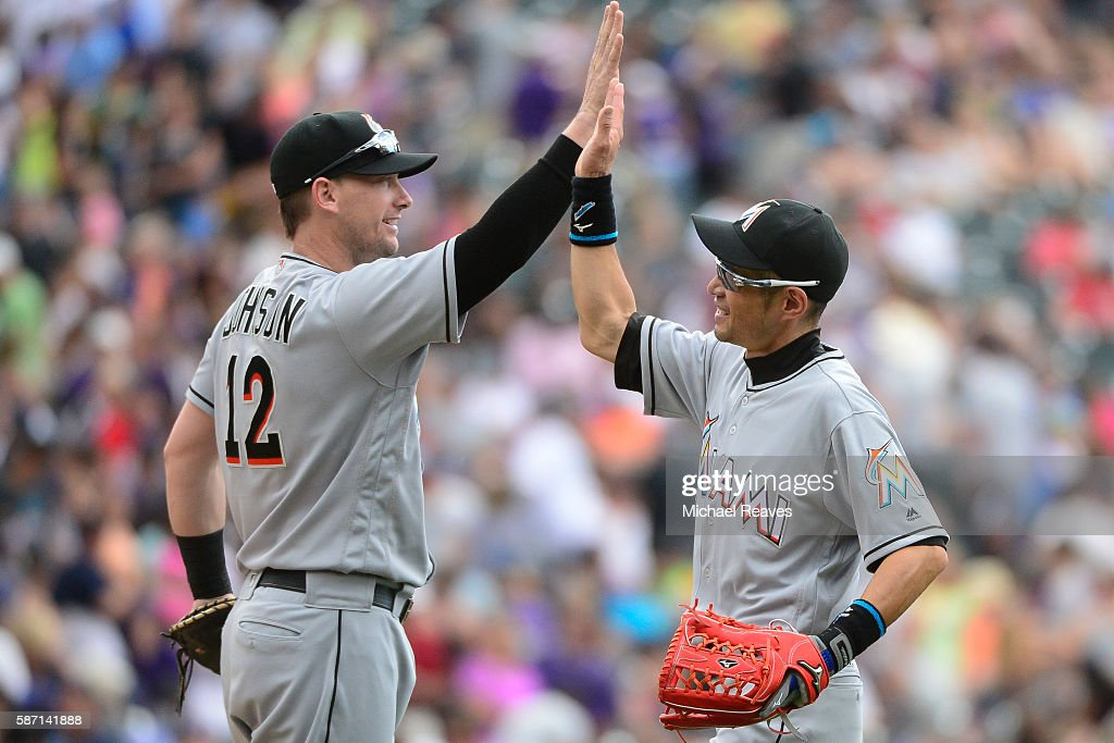 Miami Marlins first basemen Chris Johnson high fives outfielder Ichiro Suzuki after they defeated the Colorado Rockies 107 at Coors Field on August...