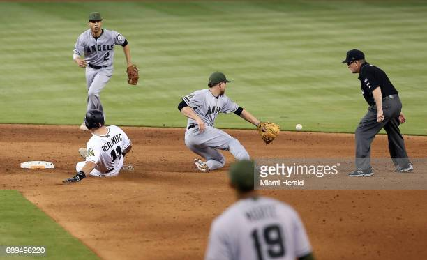 Miami Marlins' JT Realmuto slides safely into second base as the Los Angeles Angels' Nolan Fontana tries to field the ball in the sixth inning on...
