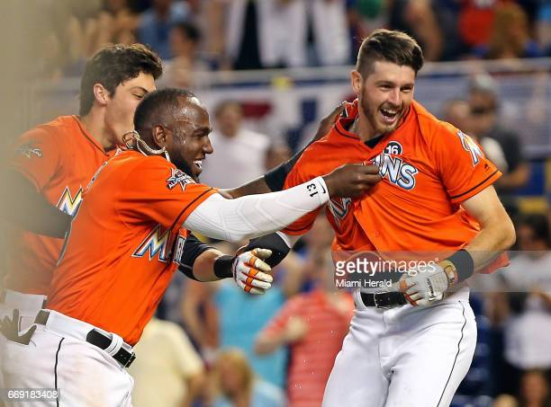 Miami Marlins' JT Riddle celebrates his walkoff homerun with teammates Marcell Ozuna and Christian Yelich as the Marlins beat the New York Mets on...