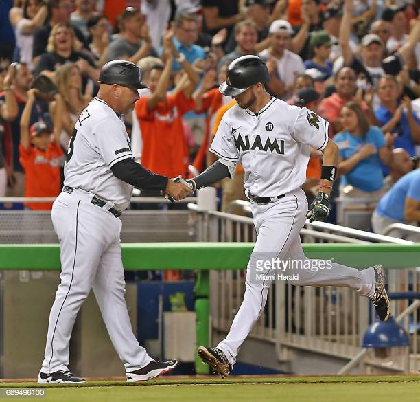 Miami Marlins' JT Riddle is congratulated by third base coach Fredi Gonzalez after his tworun home run in the fifth inning against the Los Angeles...