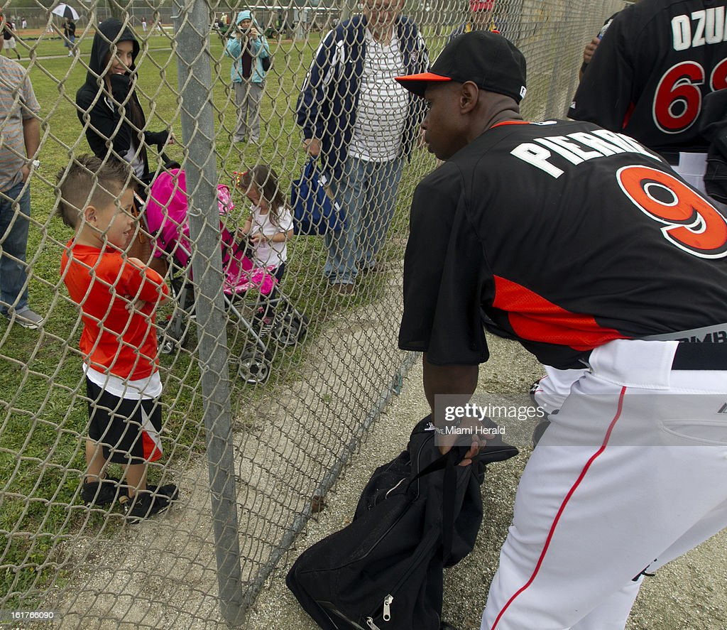 Miami Marlins' Juan Pierre, right, talks to Jaiden Delgado, 5, through the fence on the first day of full squad workouts at Marlins spring training camp at Roger Dean Stadium in Jupiter, Florida, Friday, February 15, 2013.