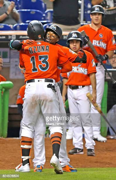 Miami Marlins' Marcell Ozuna gets a hug from teammate Dee Gordon after hitting a threerun home run in the ninth inning against the Cincinnati Reds on...