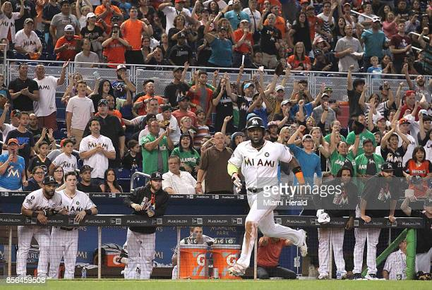Miami Marlins' Marcell Ozuna looks towards the field as he passes third base and heads to home plate with sounds of the roaring fans The Miami...