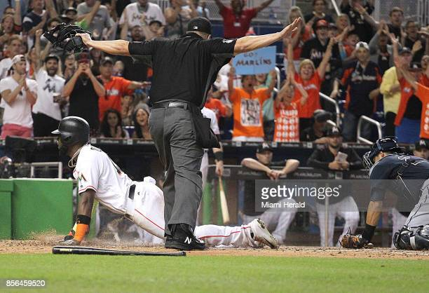 Miami Marlins' Marcell Ozuna slides into home plate to score to the delight of the roaring fans The Miami Marlins played its last game of the season...