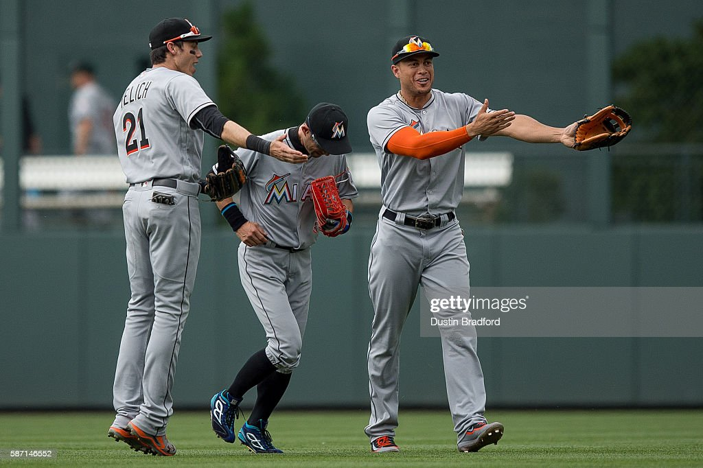 Miami Marlins outfielders, Christian Yelich #21, Ichiro Suzuki #51, and Giancarlo Stanton #27, celebrate a 10-7 win over the Colorado Rockies and the 3,000th major league hit of Suzuki earlier in the game, after a game at Coors Field on August 7, 2016 in Denver, Colorado.